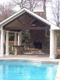 outdoor fireplace with stone bar and concrete paver patio
