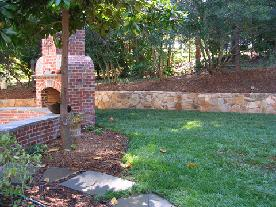 stone retaining wall opens up yard behind fireplace
