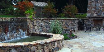stone fireplace, patio and water feature