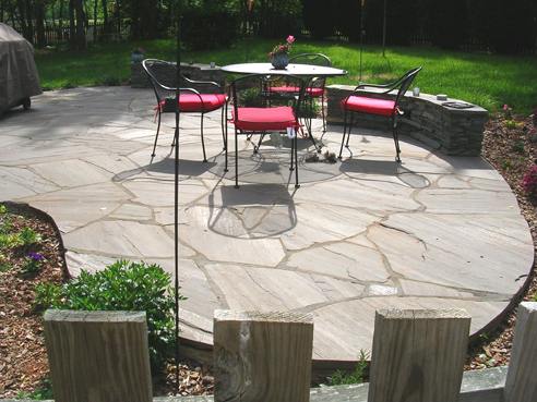 irregular bluestone patio with stacked stone sitting benches
