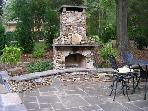 stone fireplace with bench and bluestone patio